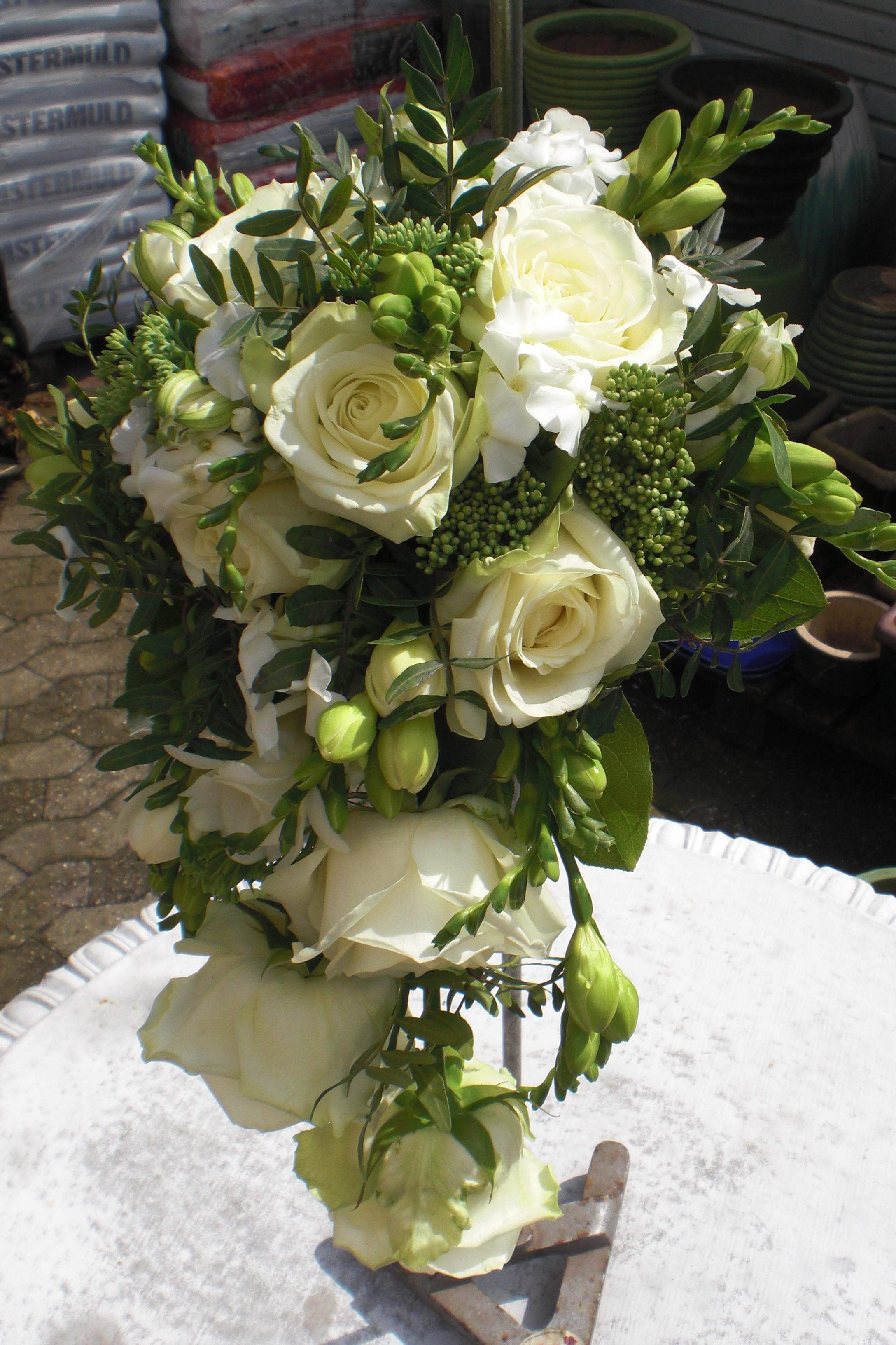 1. Brudebuket med dråbe af hvide roser, fresia og andet.